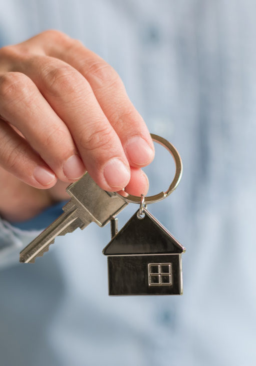 House key in real estate sale person or home Insurance broker agent's hand giving to buyer customer